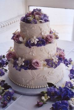 Soft pastel, fresh floral wedding cake in white, lavender, purple, violet, blush, dusty rose, and mauve.