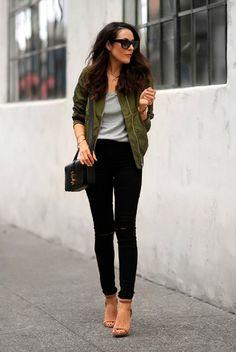 Street style look com blusa cinza, bomber jaquet verde militar, calça preta e sapato nude.