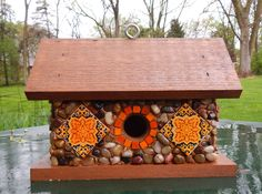 """Cedar birdhouse with stones and river rock collected from the shores of Lake Michigan, local rivers and from creek beds. Recycled embellishments of hand painted Mexican tiles and miniature glazed tiles. Suitable for outdoor or indoor décor.   7 3/4"""" high X 10 3/4"""" wide  X 5"""" deep      1 1/4"""" opening"""