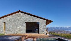 Этот современный каменный и деревянный дом имеет деку со встроенным в спа.