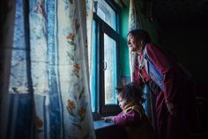 Grandmother and her granddaughter looking outside of their home window
