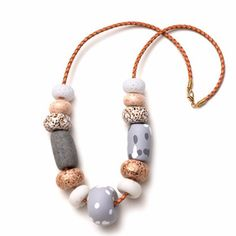 """This necklace features a variety of sparkly, patterned and spotty hand-formed polymer clay beads threaded onto tan braided leather cord. The beads range between approximately 1"""" and 2"""" diameter. Emily"""