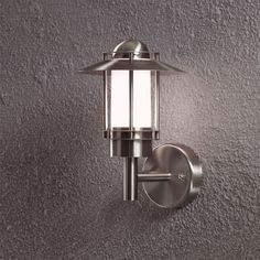 Konstsmide 7331-000 1 light stainless steel outdoor wall light with opal coloured glass.  Height: 24cm, Width: 16cm, Projection: 18cm.  Requires 1x 25W G9 capsule lamp. Lamp not included. IP44 rated.