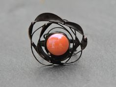 Solar system in a ring. Unique designer cocktail ring with bright orange Sun and orbiting it planets. Very special artistic piece of jewellery.  The ring is designed and handmade by me using stained glass and then embellished with the intricate decorative metal details. It is securely attached to the adjustable ring base. I have used special jewelers patina to turn the metal dark, aged and then sealed with special jewelers seal. The ring does not contain lead or nickel.  Stained glass will…