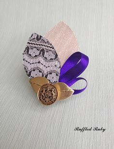 Cream & lace leaf buttonhole combined with loops of purple satin ribbon embellished with mini gold leaves and gold vintage button. www.ruffledruby.com