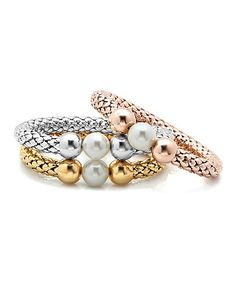 Nothing says chic like an armful of shine. These stainless steel stretch bracelets make an exceptionally svelte set thanks to their lustrous gold plating, artfully textured bands and polished pearl centerpieces.