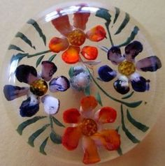 LARGE VINTAGE REVERSE CARVED & PAINTED FLORAL LUCITE BUTTON.