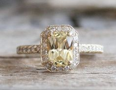 14K yellow gold milgrain halo diamond engagement ring featuring a natural radiant cut light yellow champagne sapphire measuring 7.5 x 5 mm and