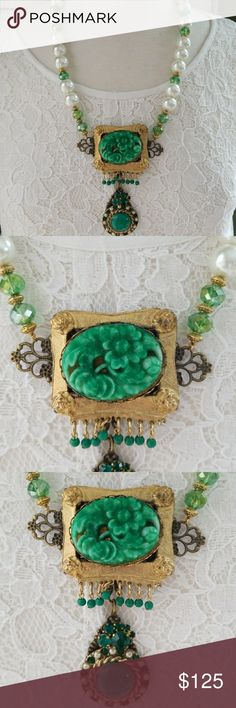 Handmade Repurposed Vintage Assemblage necklace Handmade  One of a kind Chunky white pearls and Green crystals make up the necklace  Gold spacer beads  Toggle closure Pendants consist of One 1940's carved flower cameo brooch set onto a filigree stamping. Hanging from the pendant is an emerald crystal cluster and a 1920s-1930s glass stone pendant with jade color center, emerald crystals and cream pearls I have not added pearls to the 1920s pendant, a few are missing. I prefer go keep my…