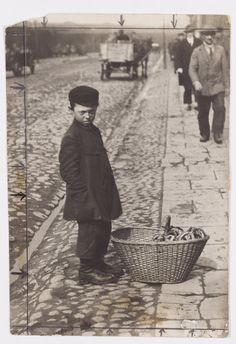 Warsaw. A boy standing by his basket of bagels at the curb. 'The merchant with his bagels has to beware of a policeman because he's peddling without a license.'