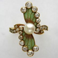 An Art Nouveau enamel, pearl and diamond ring.