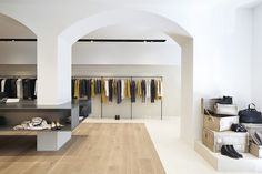 One area of the floor, covered in natural wood planks, is encased in the marble and it defines the central part of the store space, besides acting as a contrast to the backlit source of light hanging from the central area of the ceiling.