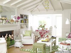 In the living-dining area of a Balboa Island, California, beach cottage, a vintage coffee table and stools in Hable Construction's Sweet Pea Beads sits on a zebra-print rug by Jonathan Adler.