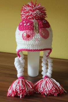Crochet cap for winter with butterfly - I like the curly-q's hanging from the ear flaps :)
