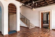 In the loggia, the staircase ascends to the second floor. The archway at left leads down to the full-size basement. The living room is beyond the double doors. Photo by Andy Frame, courtesy of Brown Harris Stevens