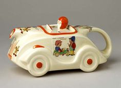Cream teapot in a car shape with handle at the rear