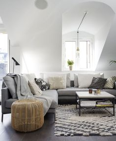 Gray  white living room with sloped ceilings. Kind of loving the Maria Löw rug.