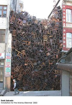 An unlikely number of chairs stacked in an unlikely way + an unlikely location.