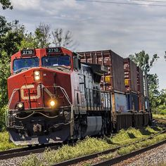 A pair of Dash 9s one in the front one in the back leads one of the few cross country intermodal trains. This train originating from Prince Rupert British Columbia is bound for Montreal. Train ID Q186 Locomotive(s) #IC2710 C44-9W & DPU #CN2662 C44-9W Location Darlington Ontario Canada Date July 24 2015