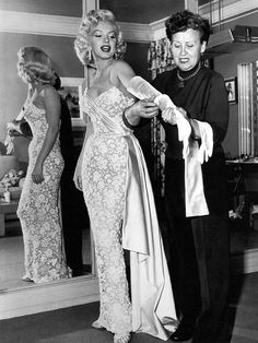 1950Marilyn in Travilla's sumptuous gown of white lace over nude crepe embellished by thousands of tiny opalescent sequins, a sash of white satin and matching train completed the look.