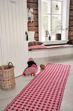 wooden bench under the window, covered with a folded carpet and some pillows.  love the chequered red rug and that toddler crowling obviously outside the carpet. . panca di legno sotto la finestra, coperta con un tappeto ripiegato e dei cuscini per renderla confortevole. lungo tappeto a quadretti rossi, e un bimbetto che gattona fuori dal tappeto.  L U N D A G Å R D | inredning, familjeliv, byggnadsvård, lantliv, vintage, färg & form #windowbench Swedish Cottage, Swedish House, Swedish Interior Design, Interior Decorating, Yoga Studio Design, Red Rugs, Scandinavian Interior, Log Homes, Decoration