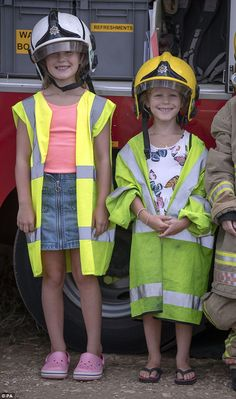 Autumn and Peter Phillip's daughters Savannah (left) and Isla (right) try on firefighters ...