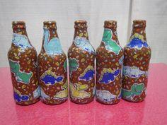 Reciclando, garrafas de vidro encapadas com tecido tricoline de dinossauros, para decorar as mesas da festa de aniversário