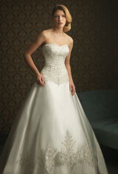 Allure Bridals: Signature Allure embroidery and Swarovski crystals make this ball gown stunning. The fitted bodice features a slightly scooped neckline and rich embellishment throughout. Sparkling crystals and embroidery continue to adorn the hem and train of the satin ball gown skirt.