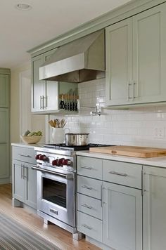 Soothing Green Kitchen Features Sage Green Cabinets Paired With White  Quartz Countertops And A White Subway