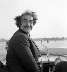 Sean Connery in Venice, 1970s. Debonair Scottish actor Sean Connery, portrayed on a water taxi with his hair in a mess because of the wind, looking behind his back, in the venetian lagoon with Venice in the background.