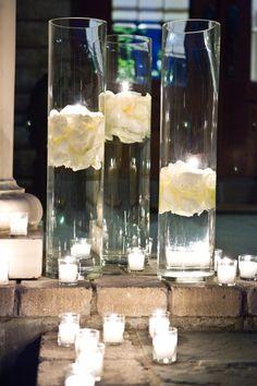 Jarrones altos con pétalos y velas flotantes