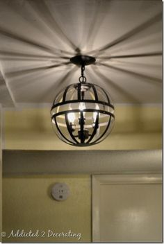 Outdated light fixture updated with two metal hanging flower baskets.