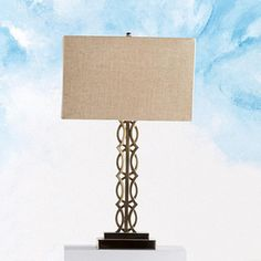 """Add a fashionable accent to your room with the 'Vitalia' table lamp, designed with an eye-catching champagne-coloured satin nickeltone base. It will add a unique touch to your bedroom, family room or living room. Resin with a champagne-coloured satin nickeltone finish 16"""" rectangular-shaped beige linen shade On/off switch on socket Uses one 100-watt (max.) type B bulb, not included Some assembly required 28"""" h."""