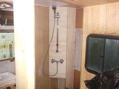 Salle de bain d'origine.Creation d'une cloison contre le lit et devant la fenetre(sans la cacher).La salle de bain fera 143cms x 98 cms au lieu de 95 x 98cms,equipee d'une douche,lavabo et wc.Fabriquation d'une structure pour le plan de toilette et etagere,le wc reste a ca place.J'avais oublie de preciser que lors de l'arrachage du lino des murs,une surprise m'attendee:fuite au dessus de la fenetre,donc reparation.Creation d'une colonne de douche en angle.Creation d'une assise sur le passage…