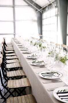 entertaining for wedding reception dinner birthday engagement party french country style: wooden french cafe chairs, beige canvas tablecloth, black white striped napkins, green plants, table centrepieces