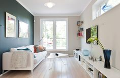 Small space living nordic style - white decor, accent wall, light wood floors, long low bookshelf, lots of light Narrow Living Room, Home Living Room, Living Spaces, Small Living, Small Apartments, Small Spaces, Low Bookshelves, Multifunctional Furniture, White Decor