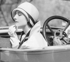 Actress Norma Shearer powdering her chin while sitting in the passenger seat of a car, 1929.