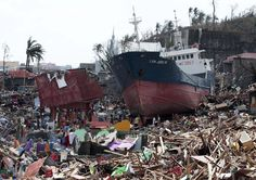 Survivors walk past a ship that lies on top of damaged homes after it was washed ashore in Tacloban city, Leyte province central Philippines. Philippines Cities, Giant Waves, Leyte, Climate Action, Natural Disasters, Southeast Asia, The Incredibles, Ocean, Brazil