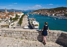 Picture of a woman admiring the view from Kamerlengo Fortress over the waterfront in Trogir, Croatia