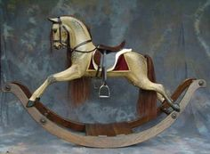 Legends' own rocking horse carving design finished in an 'old' style with natural dappling    Burgundy saddle blanket with gold trim, Havana leather tack and dark brown mane and tail.    Dark oak bow.    May be finished in a traditional style rather than natural dappling and available on bow or safety stand.