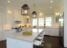 Kitchen Cottage. Cottage Kitchen Design. White Cottage Kitchen. White coastal kitchen Ideas. Stunning U-shaped kitchen with white cabinetry accented with brushed nickel hardware alongside white quartzite countertops with a subway tiled backsplash. The kit