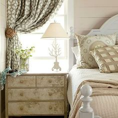A vintage chest was faux-painted and sealed with a crackle glaze. A graphic print on the custom curtains brings modern style to the neutral palette and linens. Coastalliving.com