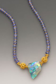 Glory Australian boulder opal displays layers of riotous dichroic color. On faceted tanzanite with18K gold accents.