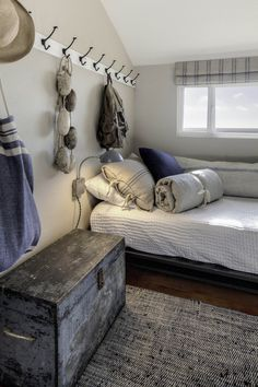 Teen Boy's Room - nautical vibe, cotton stripe linens and valence, grain sack pillow, rag rug, boards with hooks for storage, metal wall sconces hang by the bed, painted wood chest