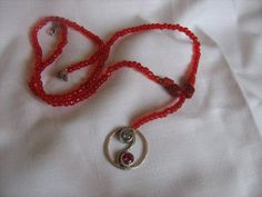 Yin Yang pendant with blue and red cubic's on a red beaded necklace.