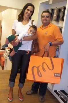 Virna Dias, jogadora de voleibol, confere os  lançamentos da coleção Eurico Max  (com seu filho e o vendedor Renato)