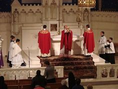 Elevation during the liturgy of the Eucharist. Red vestments for Reformation Day or Pentecost.