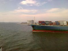 Cargo ship leaving for sea.  A scene from Fort Kochi, Vypeen LNG terminal is seen in the background.