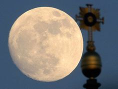 The moon rises behind the cross of the Frauenkirche (Church of Our Lady) in Dresden, Germany on May 4, 2012.