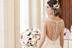 This Diamante-beaded wedding dress from Stella York features lace and tulle with a fitted sweetheart bodice and beaded shoulder straps that gather and fall into an intricate draped back design of sparkling jewels. The skirt flows full with layers of billowy tulle. The back zips up with ease under Stella crystal buttons. (sp)